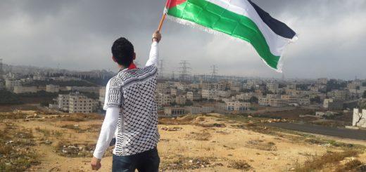 Palestinian identity - holding a Palestinian flag aloft